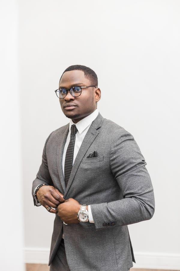 Jeune homme d'affaires d'Afro-américain dans un costume gris attachant un lien sur un fond blanc photo stock