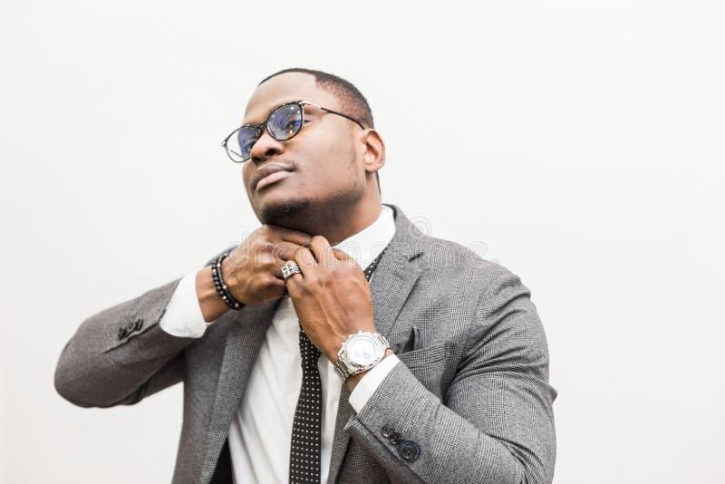 Jeune homme d'affaires d'Afro-américain dans un costume gris attachant un lien sur un fond blanc photos libres de droits