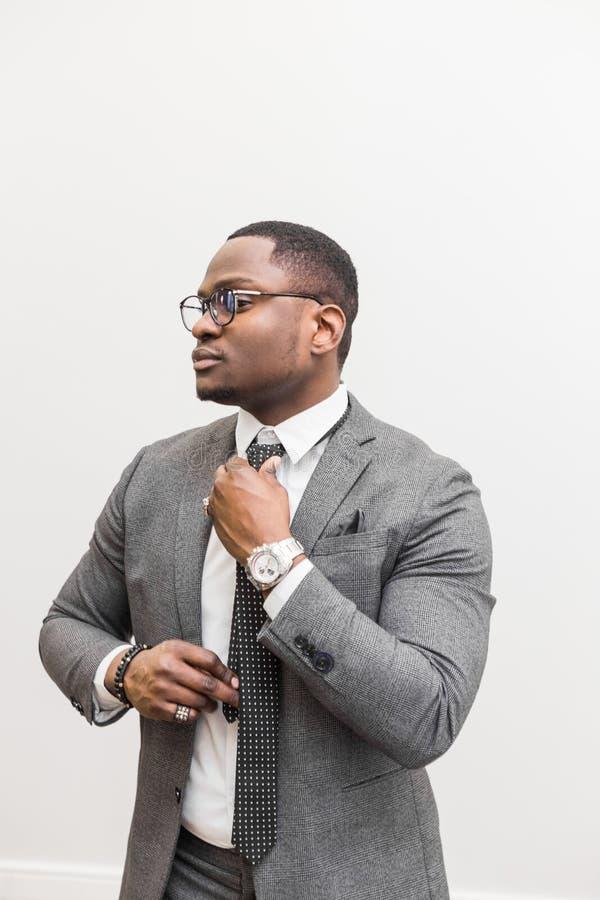 Jeune homme d'affaires d'Afro-américain dans un costume gris attachant un lien sur un fond blanc image stock
