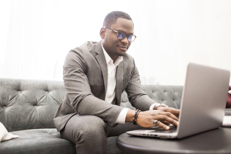 Jeune homme d'affaires d'Afro-américain dans un costume gris fonctionnant derrière un ordinateur portable photo libre de droits