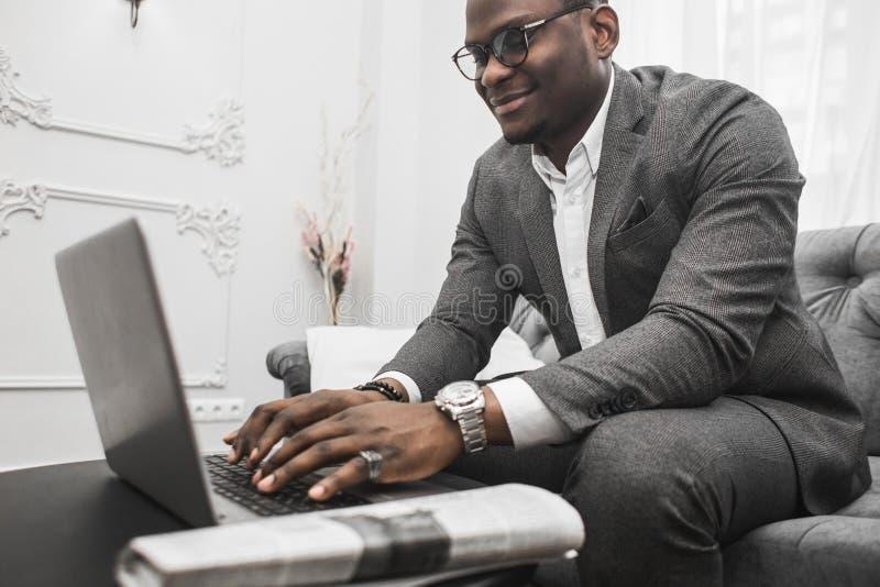 Jeune homme d'affaires d'Afro-américain dans un costume gris fonctionnant derrière un ordinateur portable images libres de droits