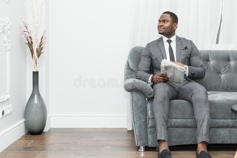 Jeune homme d'affaires d'Afro-américain dans un costume gris lisant un journal tout en se reposant sur un sofa photos libres de droits