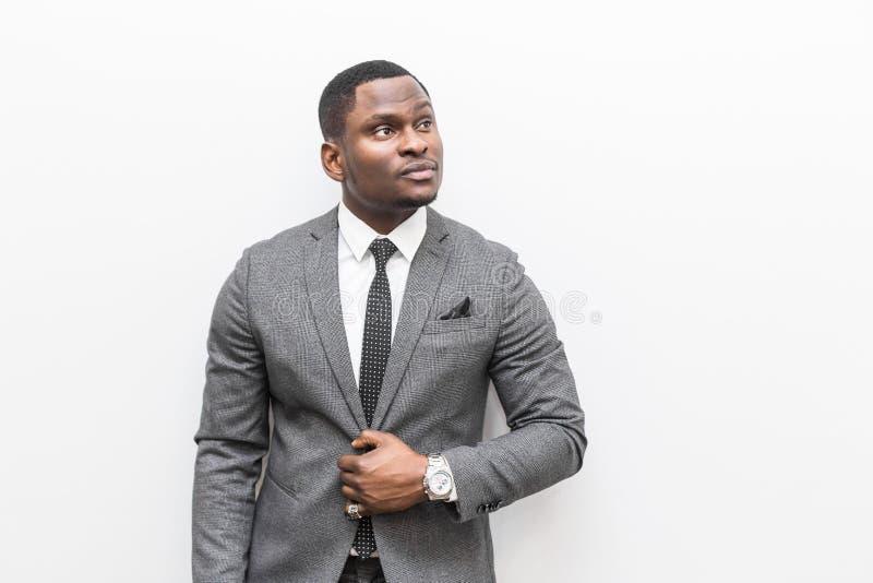 Jeune homme d'affaires d'Afro-américain dans un costume gris sur un fond blanc photo stock