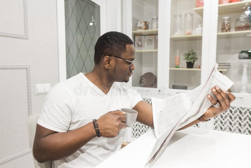 Jeune homme d'affaires d'Afro-américain lisant un journal au petit déjeuner photographie stock