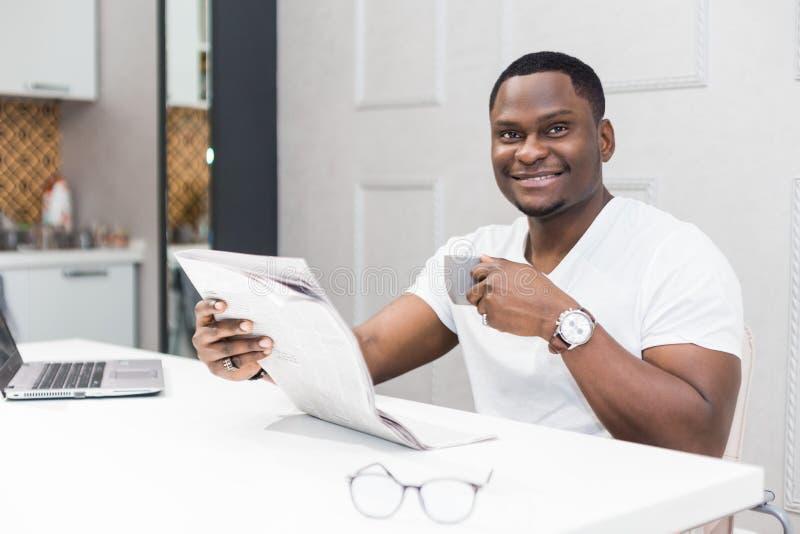 Jeune homme d'affaires d'Afro-américain lisant un journal au petit déjeuner photographie stock libre de droits