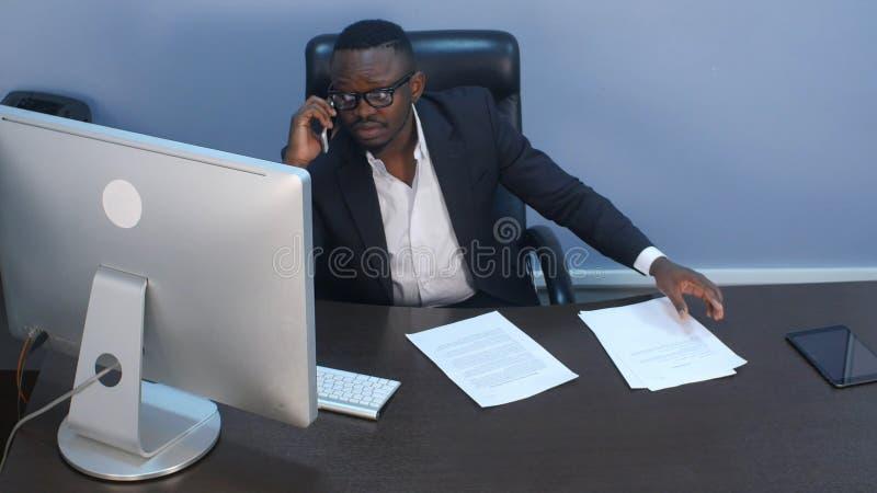 Jeune homme d'affaires afro-américain songeur ayant un appel téléphonique, discutant des documents et s'asseyant dans le bureau photo libre de droits