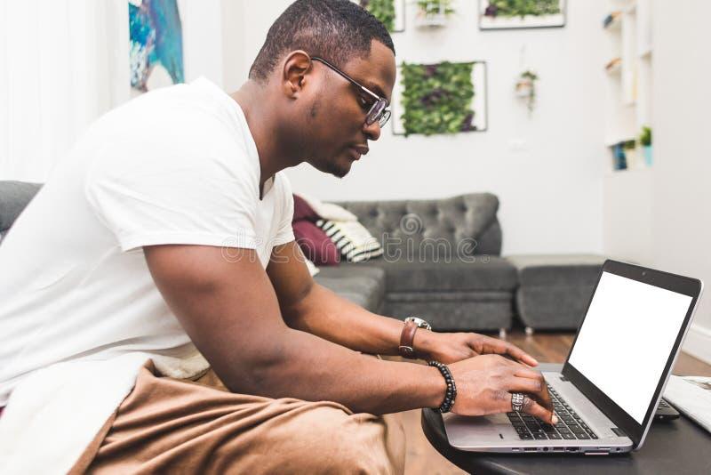 Jeune homme d'affaires d'Afro-américain travaillant à distance à la maison sur un ordinateur portable images libres de droits