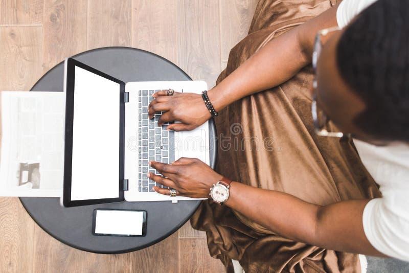Jeune homme d'affaires d'Afro-américain travaillant à distance à la maison sur un ordinateur portable photos libres de droits