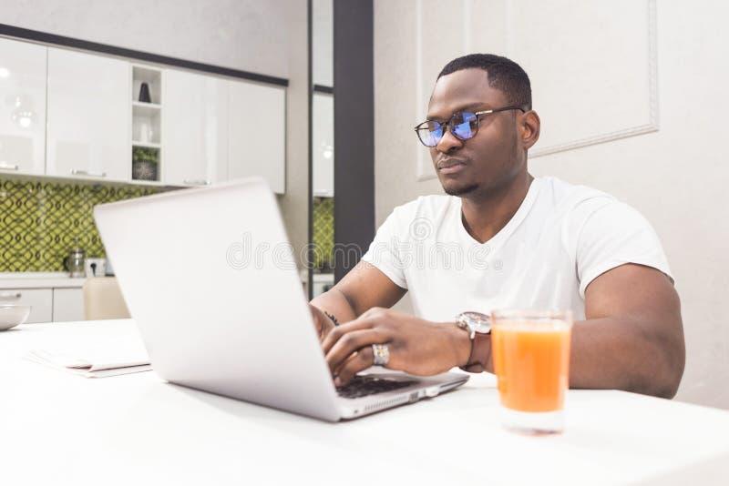 Jeune homme d'affaires d'Afro-américain travaillant sur un ordinateur portable dans la cuisine dans un intérieur moderne photographie stock libre de droits