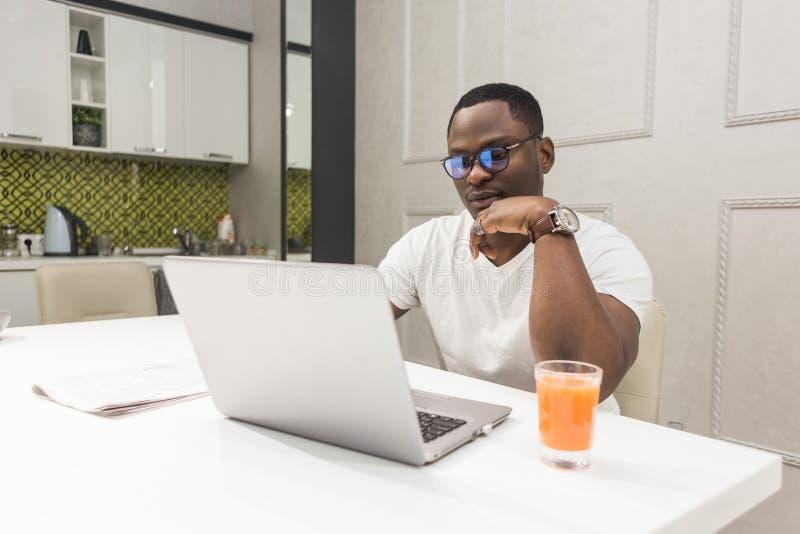 Jeune homme d'affaires d'Afro-américain travaillant sur un ordinateur portable dans la cuisine dans un intérieur moderne images libres de droits