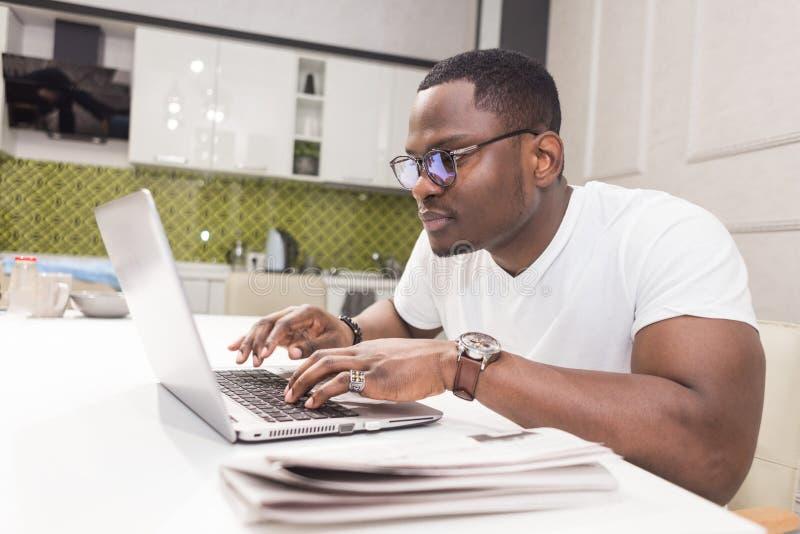 Jeune homme d'affaires d'Afro-américain travaillant sur un ordinateur portable dans la cuisine dans un intérieur moderne image libre de droits