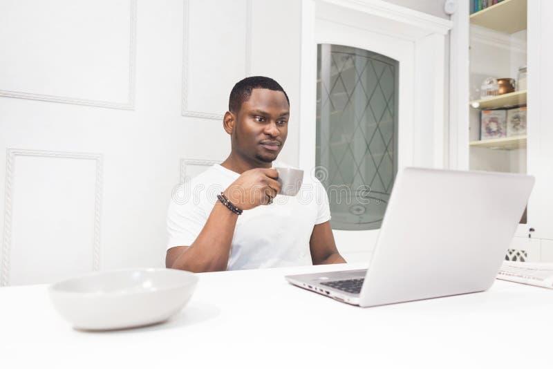 Jeune homme d'affaires d'Afro-américain travaillant sur un ordinateur portable dans la cuisine dans un intérieur moderne images stock