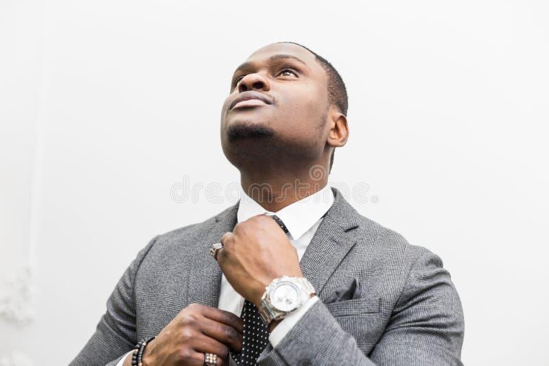 Jeune homme d'affaires d'Afro-am?ricain dans un costume gris attachant un lien sur un fond blanc photo libre de droits