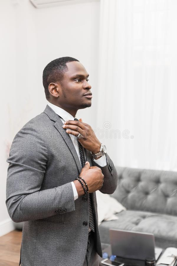Jeune homme d'affaires d'Afro-am?ricain dans un costume gris attachant un lien sur un fond blanc photos stock