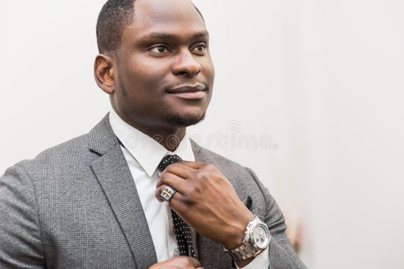 Jeune homme d'affaires d'Afro-am?ricain dans un costume gris attachant un lien sur un fond blanc photographie stock libre de droits