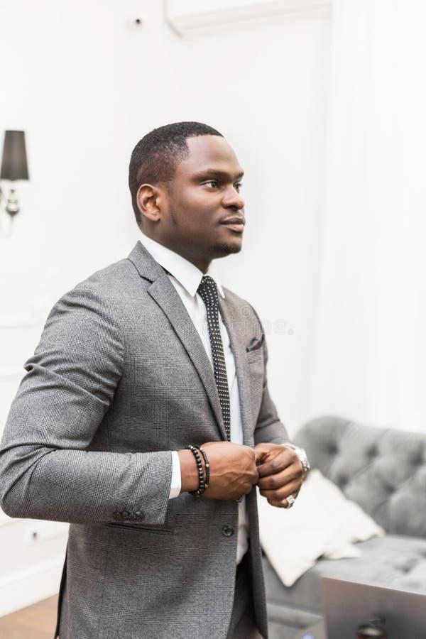 Jeune homme d'affaires d'Afro-am?ricain dans un costume gris attachant un lien sur un fond blanc images stock