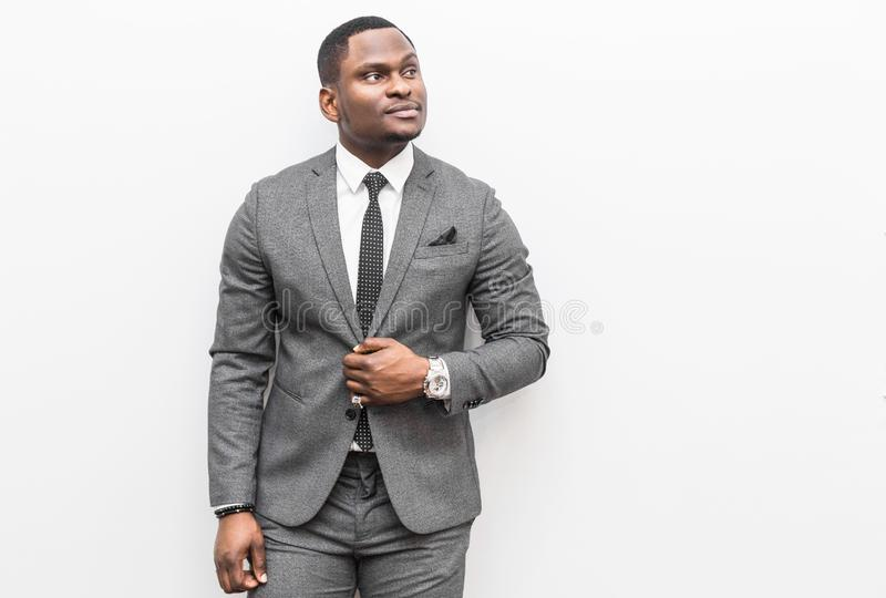 Jeune homme d'affaires d'Afro-am?ricain dans un costume gris sur un fond blanc image libre de droits