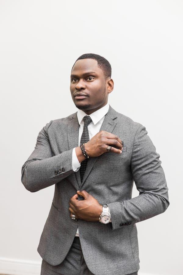Jeune homme d'affaires d'Afro-am?ricain dans un costume gris sur un fond blanc images libres de droits