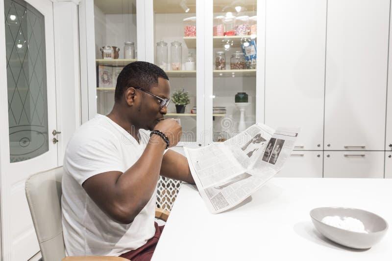 Jeune homme d'affaires d'Afro-am?ricain lisant un journal au petit d?jeuner photographie stock libre de droits