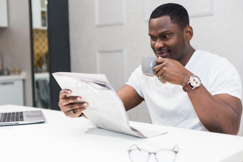 Jeune homme d'affaires d'Afro-am?ricain lisant un journal au petit d?jeuner image libre de droits