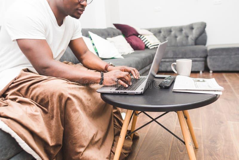 Jeune homme d'affaires d'Afro-am?ricain travaillant ? distance ? la maison sur un ordinateur portable photo libre de droits