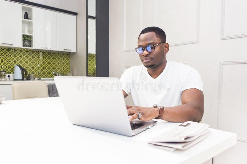 Jeune homme d'affaires d'Afro-am?ricain travaillant sur un ordinateur portable dans la cuisine dans un int?rieur moderne photo stock