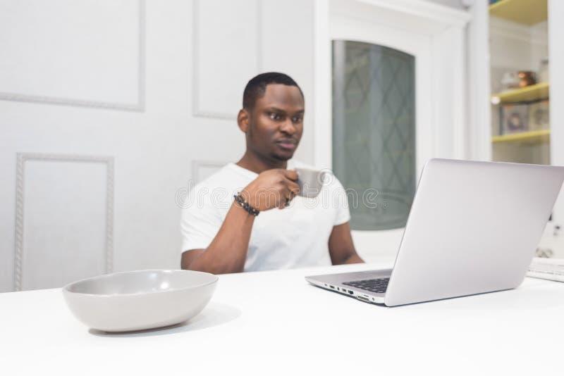 Jeune homme d'affaires d'Afro-am?ricain travaillant sur un ordinateur portable dans la cuisine dans un int?rieur moderne images libres de droits