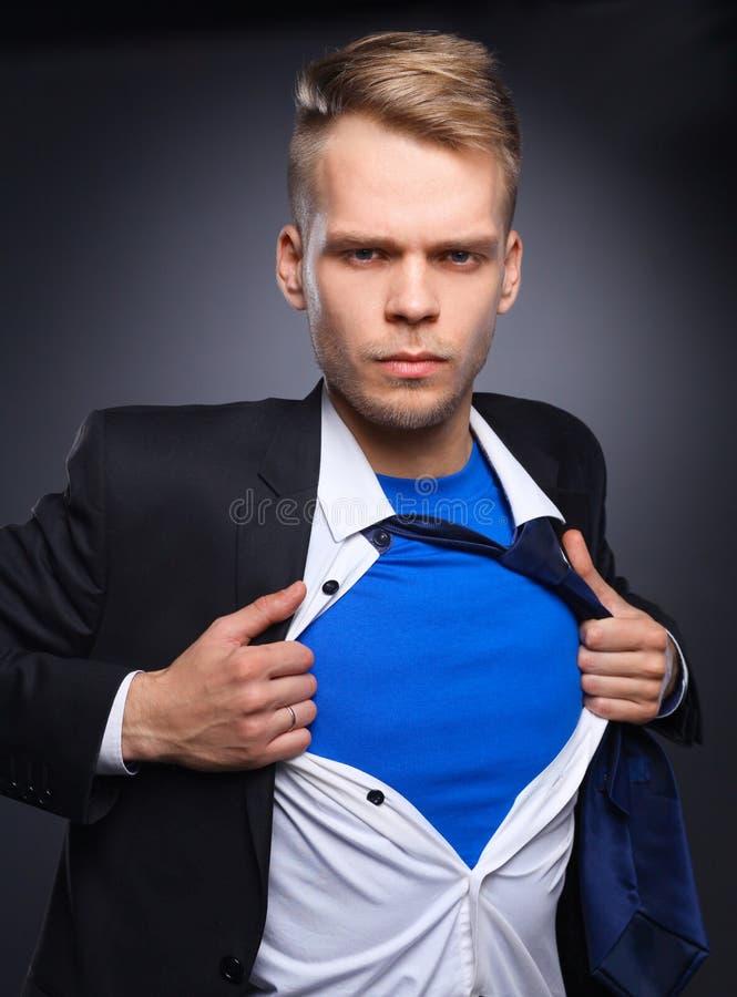 Jeune homme d'affaires agissant comme un superhéros et déchirant sa chemise, d'isolement sur le fond gris photo stock
