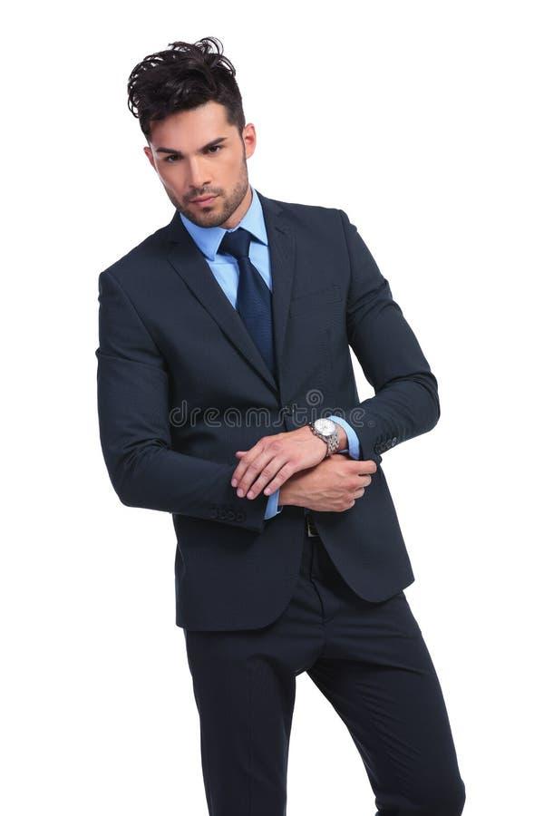 Jeune homme d'affaires ajustant la douille de son manteau photos stock