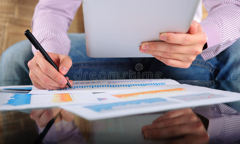 Jeune homme d'affaires analysant des diagrammes avec le comprimé numérique photos stock