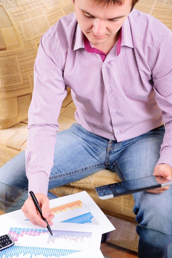 Jeune homme d'affaires analysant des diagrammes sur le sofa photographie stock