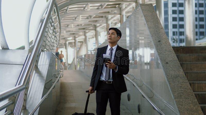 Jeune homme d'affaires asiatique avec des bagages lisant le poteau indicateur sur le lef photos libres de droits