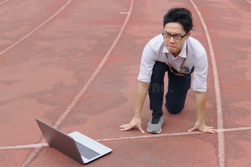 Jeune homme d'affaires asiatique avec la position de début prête d'ordinateur portable à expédier sur la voie de course Concept d image stock