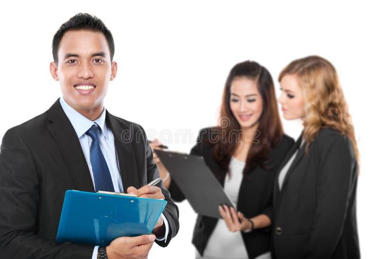 Jeune homme d'affaires asiatique, avec son équipe derrière D'isolement dans le blanc photos stock