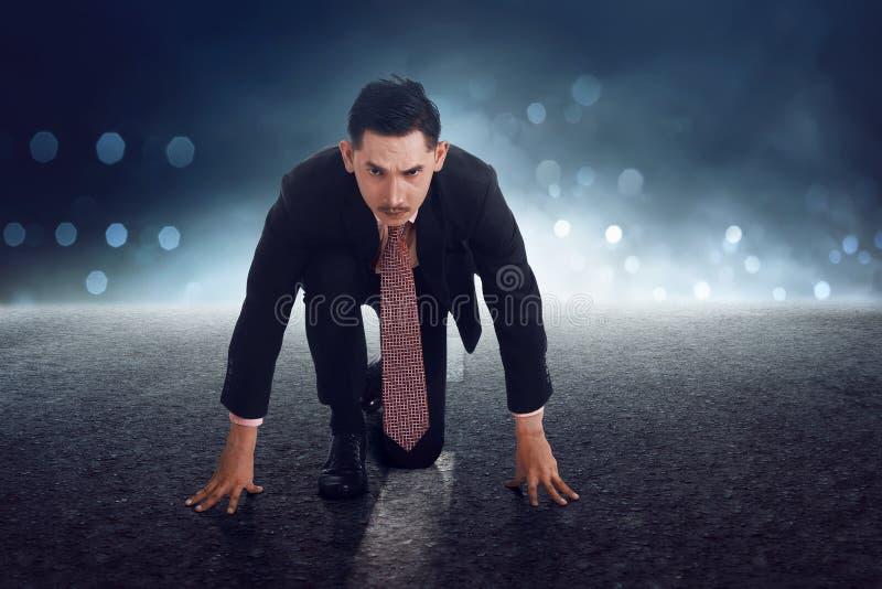 Jeune homme d'affaires asiatique en position de début étant prête pour la course photos stock