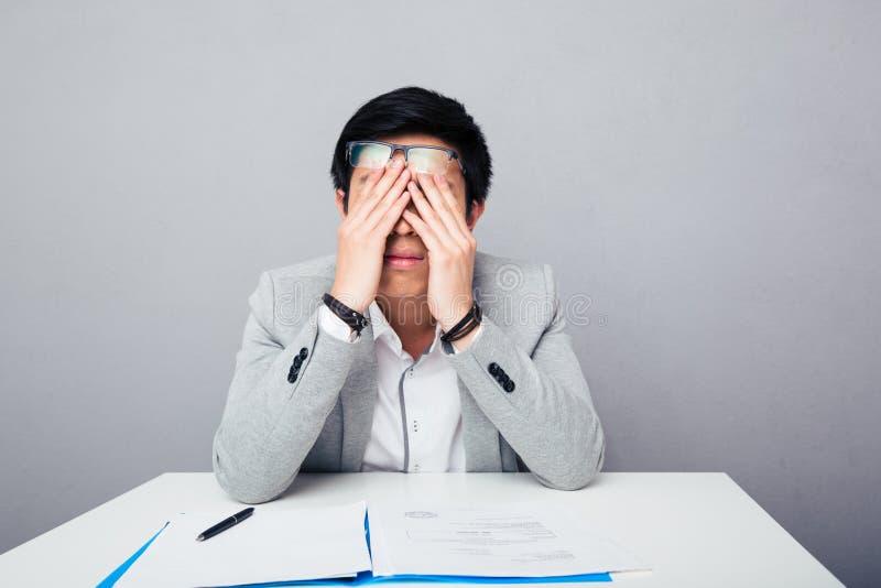Jeune homme d'affaires asiatique frottant ses yeux image stock