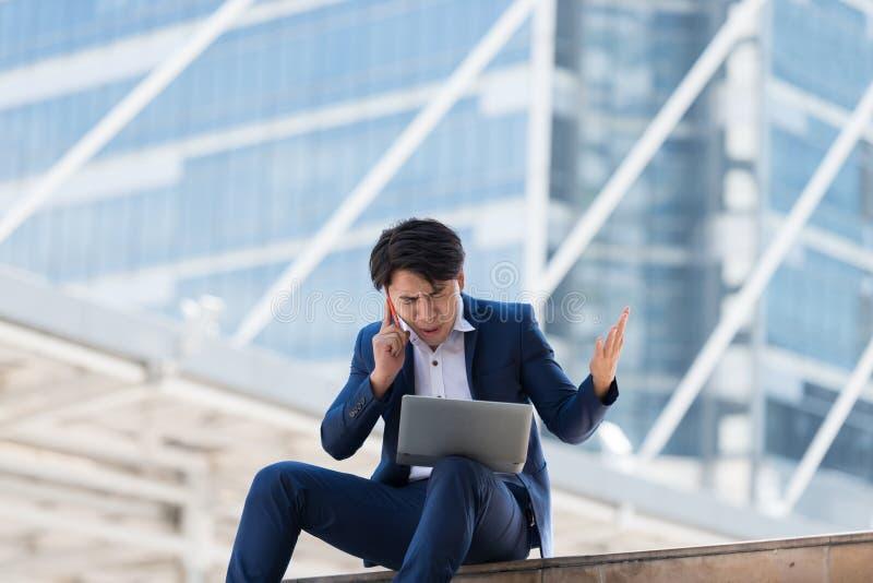 Jeune homme d'affaires asiatique parlant au téléphone portable avec un f sérieux photos stock