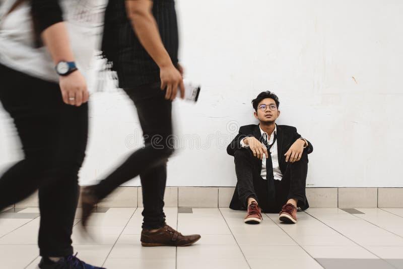 Jeune homme d'affaires asiatique sans élégance s'asseyant au passage couvert pensant à son problème photographie stock