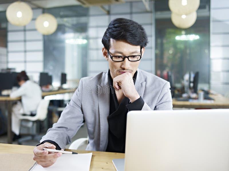 Jeune homme d'affaires asiatique travaillant dans le bureau photos libres de droits