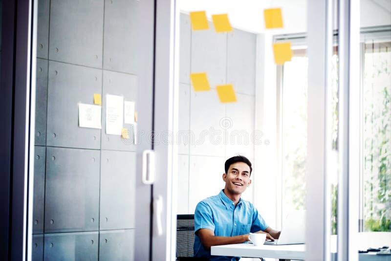 Jeune homme d'affaires asiatique Working sur l'ordinateur portable d'ordinateur dans le lieu de réunion de bureau Homme analysant image libre de droits