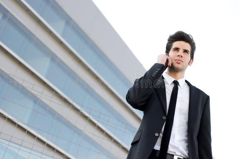 Jeune homme d'affaires attirant au téléphone dans un immeuble de bureaux photographie stock