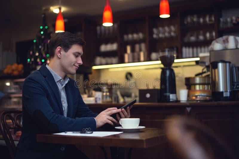 Jeune homme d'affaires attirant dans un boire de costume photo stock