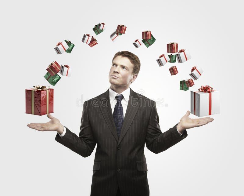 Jeune homme d'affaires avec des cadres de cadeau dans des ses mains. images stock
