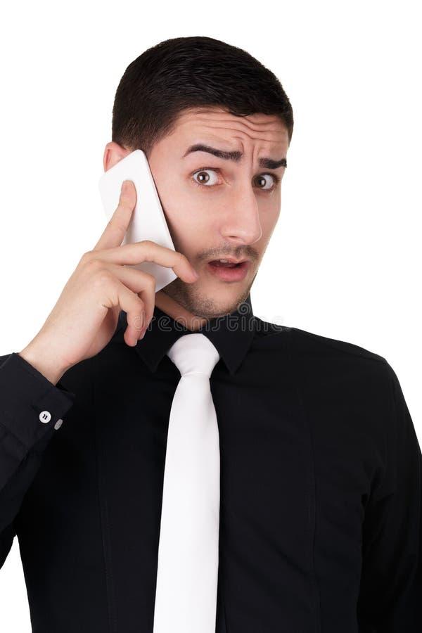 Jeune homme d'affaires avec l'expression étonnée au téléphone image libre de droits