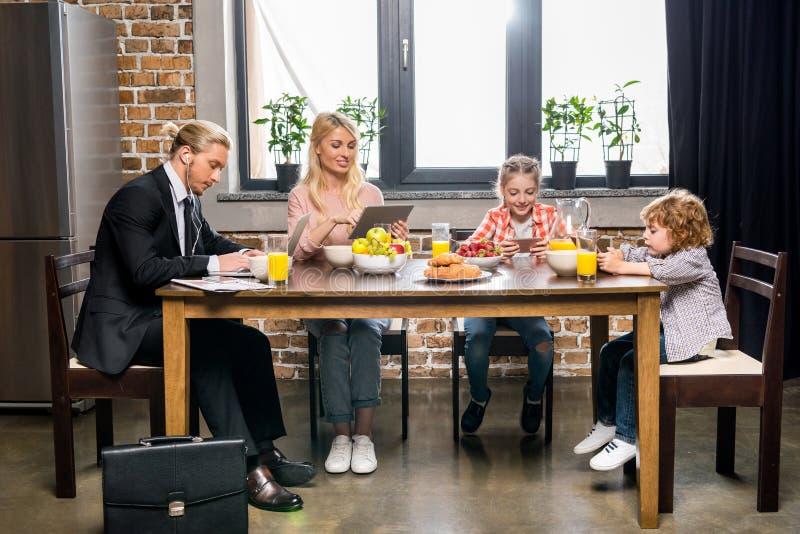 jeune homme d'affaires avec la famille prenant le petit déjeuner et à l'aide des dispositifs numériques image libre de droits