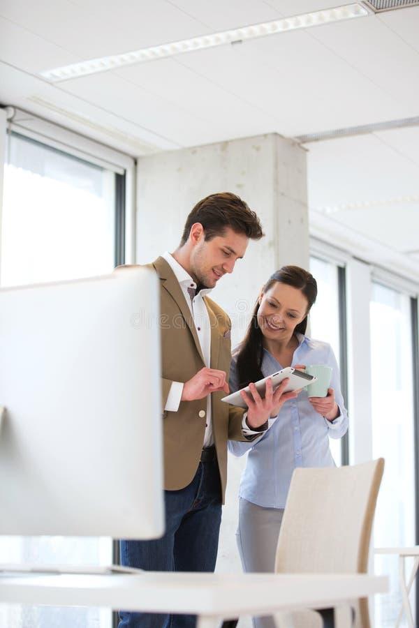 Jeune homme d'affaires avec le collègue féminin à l'aide du comprimé numérique dans le bureau photo libre de droits