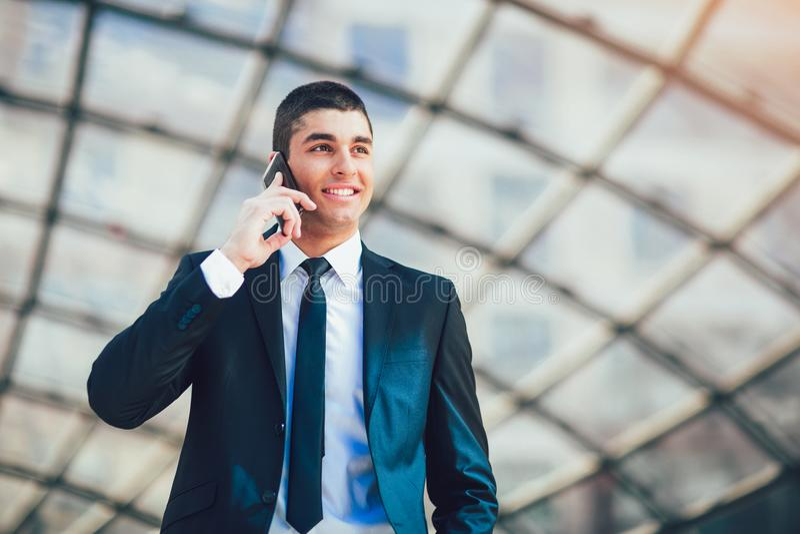 Jeune homme d'affaires avec le téléphone portable parlant de costume formel extérieur image libre de droits