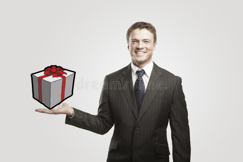 Jeune homme d'affaires avec un cadeau sur sa main. photo stock