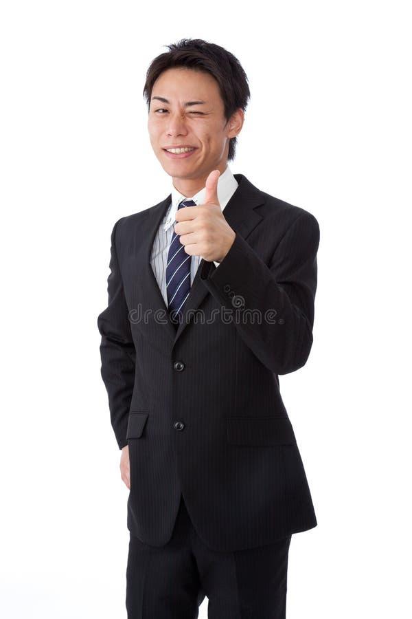 Jeune homme d'affaires avec un clin d'oeil et des pouces vers le haut photos stock