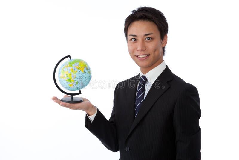 Jeune homme d'affaires avec un globe images stock